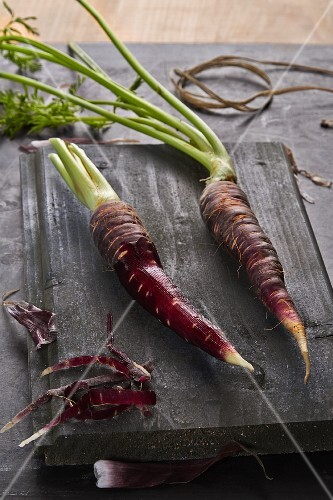 Fresh purple carrots, partially peeled