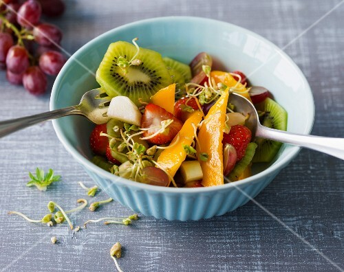 A colourful fruit salad with cereal sprouts