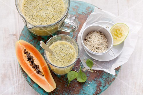 A papaya smoothie made with bananas, limes, spinach and hemp seeds