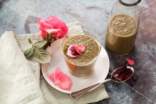 A pomegranate smoothie made with watermelon, apple, baby spinach, lime leaves and rose petals