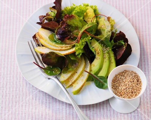 Mixed leaf salad with avocado, pears and sesame seeds