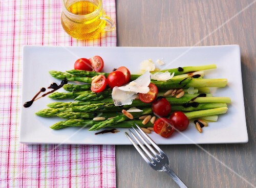 Green asparagus salad with cherry tomatoes, fresh Parmesan and pine nuts