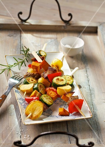Marinated meat skewers with potatoes and colourful vegetables