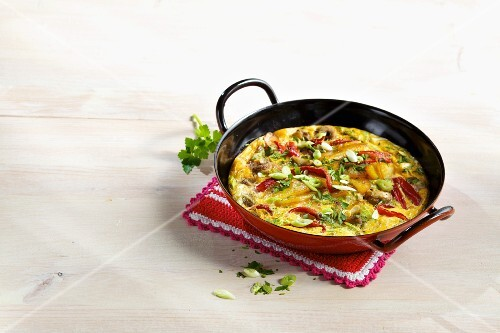 A colourful oven-baked tortilla with mushrooms, red peppers and spring onions