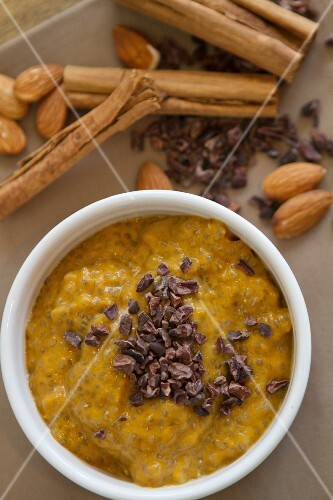 Pumpkin pudding with chia seeds, almond milk, almonds, dates, cinnamon, almond butter, maple syrup and pumpkin seeds sprinkled with cocoa