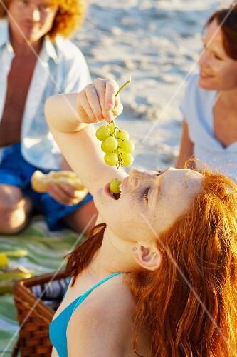 A girl eating grapes at a beach picnic