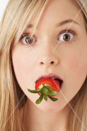 A girl eating a strawberry
