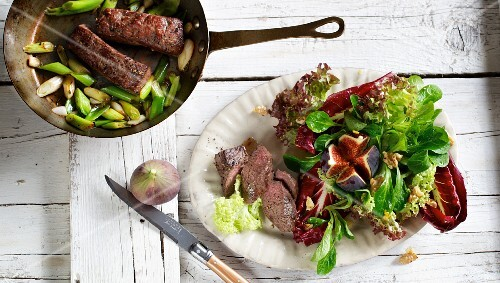 Roast lamb fillet with fresh figs on a mixed leaf salad