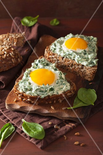 A sunflower seed roll topped with spinach cream cheese and fried eggs