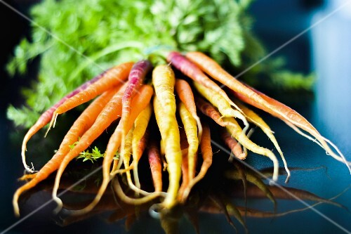 A bunch of carrots on a glass table