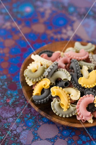 Colourful pasta on a wooden plate