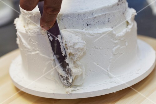 A cake being decoration with white cream
