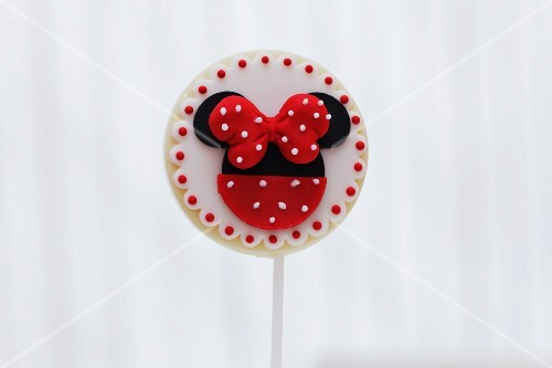 A round biscuit lolly decorated with a red bow and dots