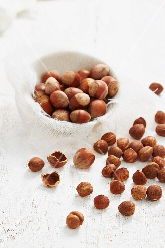Hazelnuts in and out of shells with cracked shells
