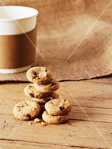 A stack of oat and raisin biscuits in front of a cup of coffee