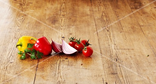 Peppers, red onions and tomatoes on a wooden surface