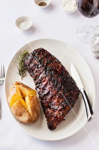 A grilled rack of ribs with a baked potato