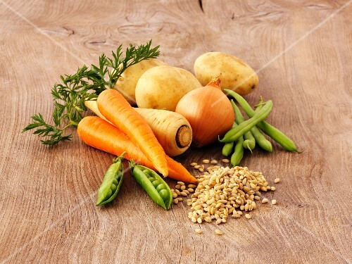 Ingredients for vegetable soup on a wooden surface