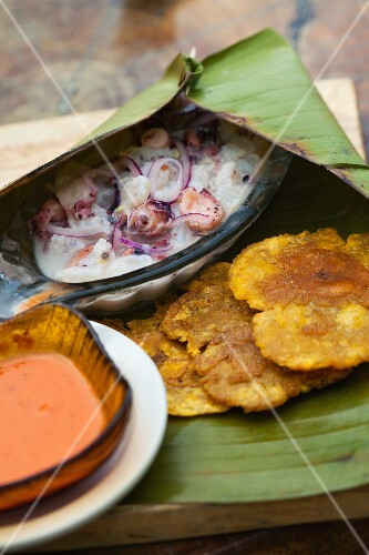 Octopus ceviche with a spicy sauce and sweet potato cakes in a banana leaf