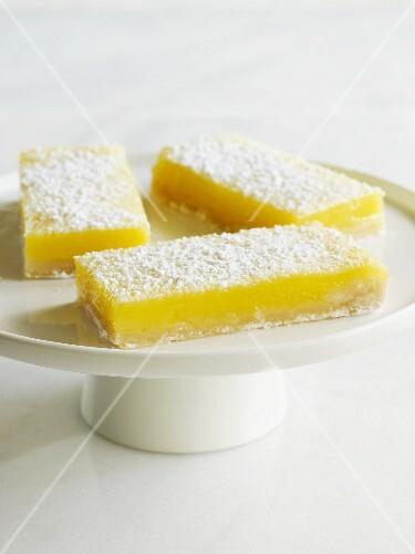 Three lemon bars on a cake stand