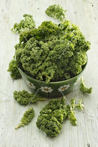 Green kale in a green bowl decorated with flowers