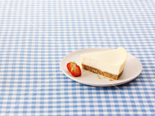 A slice of New York Cheesecake with strawberries