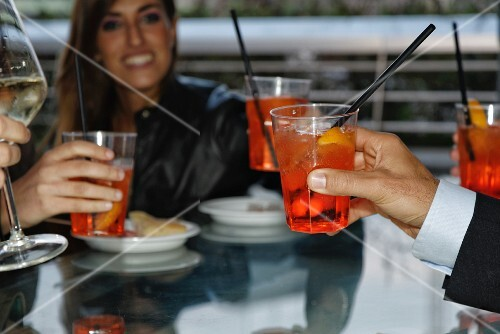 Friends raising a toast with cocktails in a restaurant