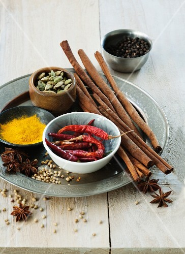 An arrangement of spices featuring cinnamon, cardamom, chillis, star anise, pepper, coriander and turmeric