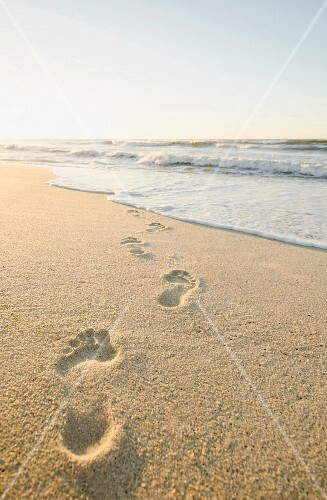 Footprints in the sand leading to the sea