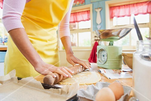 A woman in a kitchen wearing an apron rolling out pastry with a rolling pin