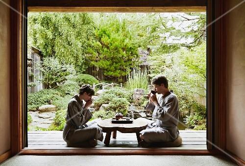 A young couple wearing kimonos sitting cross-legged on a terrace in a zen garden drinking tea