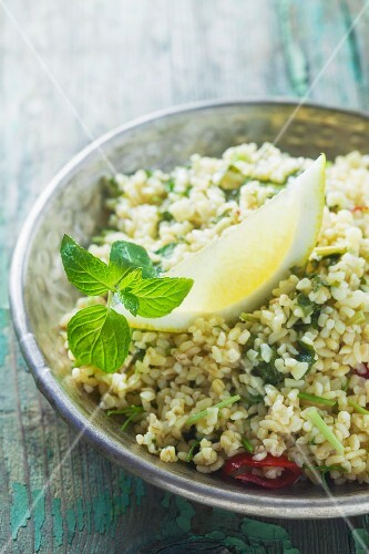 Couscous salad with lemon and mint in a metal bowl