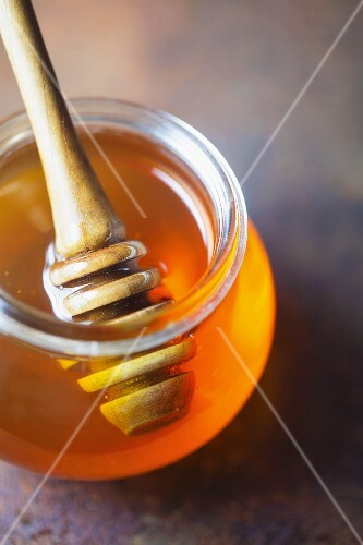 A jar of honey with a honey spoon on a metal surface