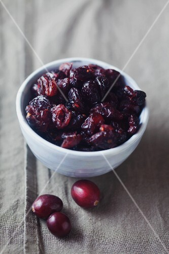 Dried cranberries in a bowl on a linen napkin