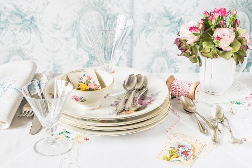 Crockery, cutlery, glasses, table cards and a bunch of flowers for an Easter table