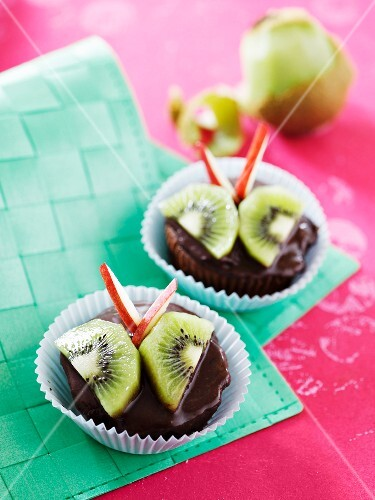 Chocolate muffins decorated with kiwi and apple 'butterflies'
