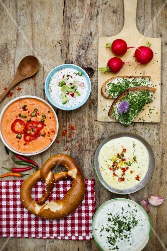Various dips, radishes and a pretzel