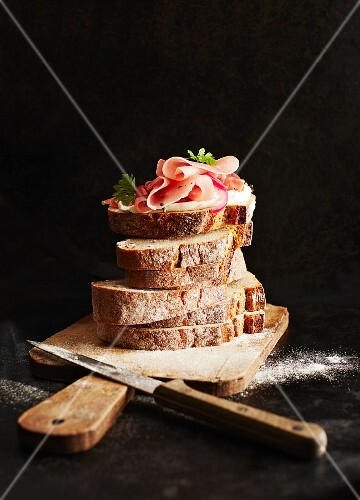 Slices of bread topped with ham on a wooden board