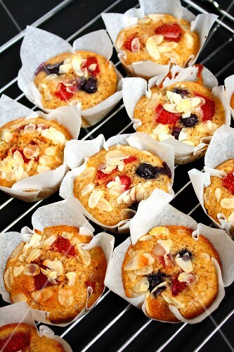 Fruit muffins with flaked almonds on a wire rack