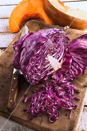 Sliced red cabbage on a chopping board with pumpkin wedges in the background
