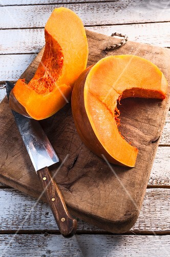 Two pumpkin wedges on a chopping board