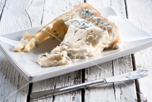 A wedge of Gorgonzola cheese on a white plate