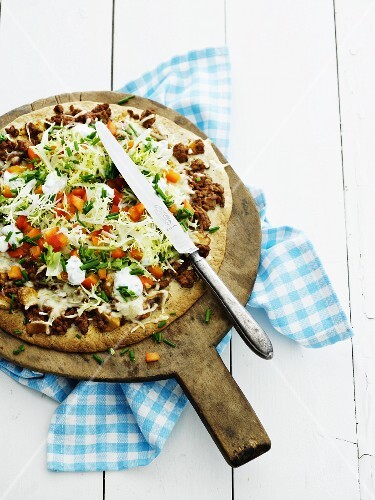 A minced meat pizza with vegetables (seen from above)