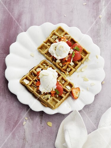 Wholemeal waffles with flacked almonds, strawberries and a scoop of ice cream (seen from above)