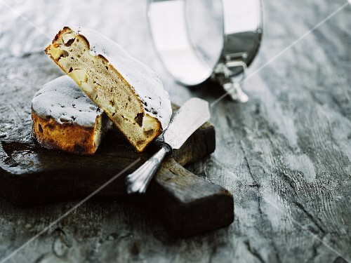 A sliced mini apple and cinnamon cake with a kitchen knife on a rustic wooden board