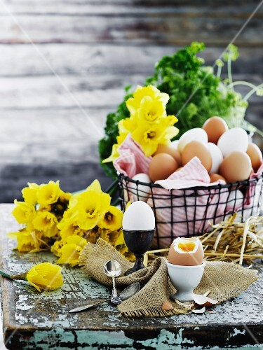 A basket of eggs, daffodils and boiled eggs on a wooden table