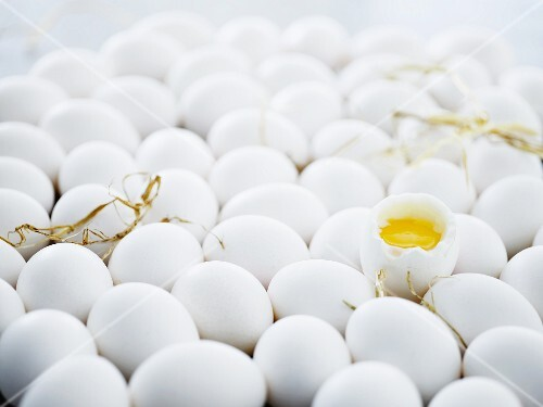 Eggs with straw and a cracked-open, soft-boiled egg