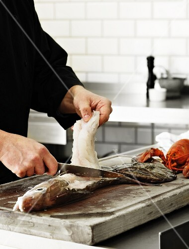 A chef filleting a fish in a kitchen