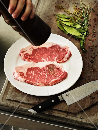 A chef seasoning raw beef steaks with ground black pepper