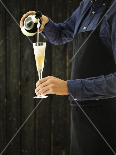 A sommelier pouring champagne into a flute